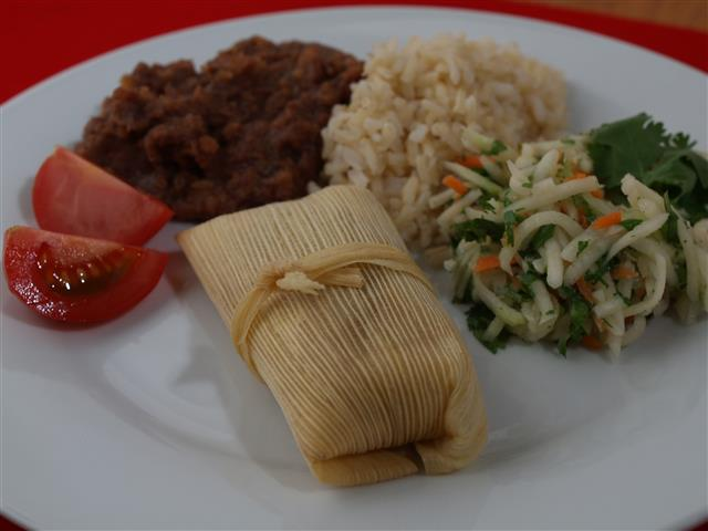 fertige Tamales mit Reis, Frijoles und Salat