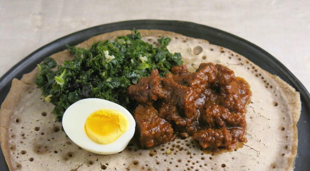 Grünkohl äthiopisch (Gomen Wot) auf Injera mit Ei und geschmortem würzigem Rindfleisch