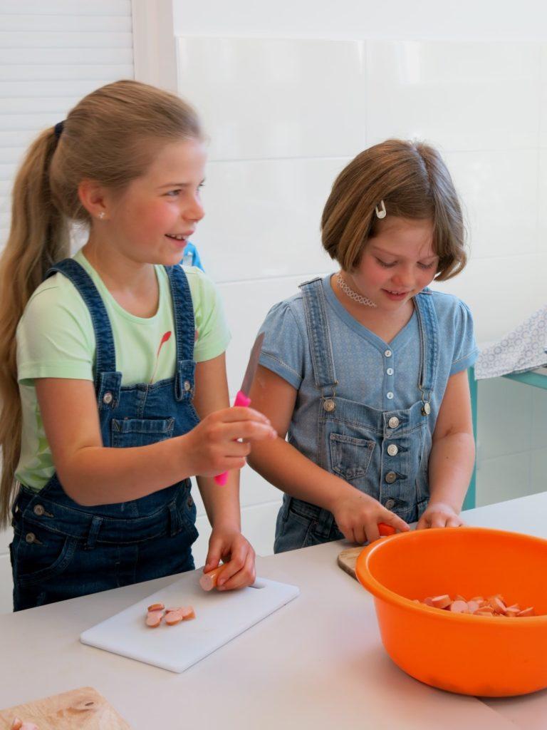 Schülerinnen schneiden Würstchen